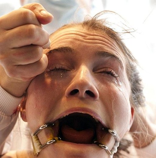 gagged woman crying as painful liquid is squirted into her eyes