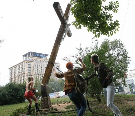 cutting down a cross with a chainsaw for Pussy Riot