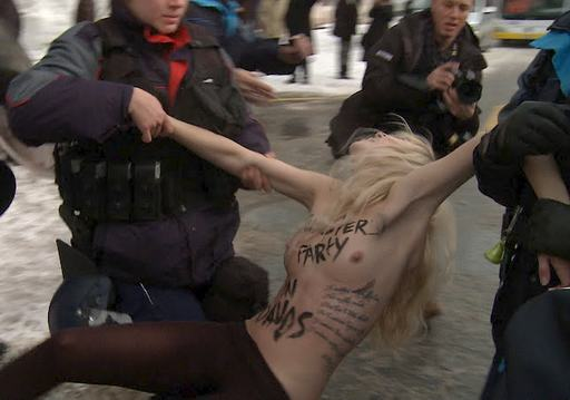 nude protester being hauled off by swiss cops