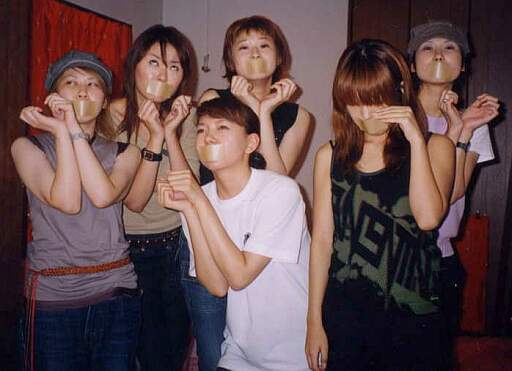 six asian girls protesting with gags on their mouths