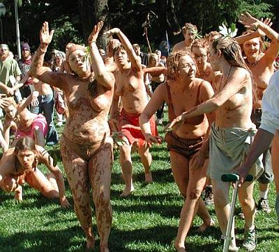 naked protesters wallowing in mud like pigs