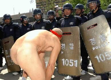 older man gets naked in front of line of riot police