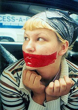 tape gagged woman protesting in public